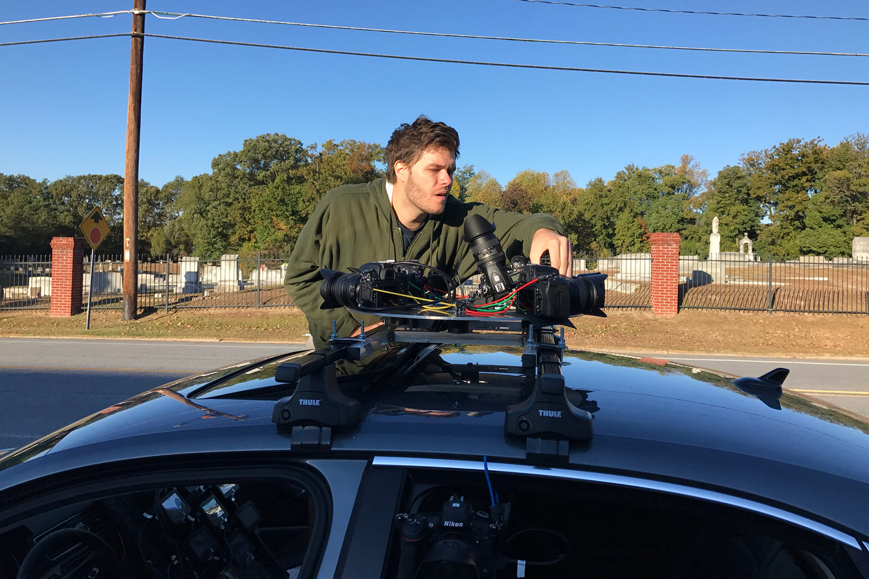 A person operates a camera rig on top of a car.