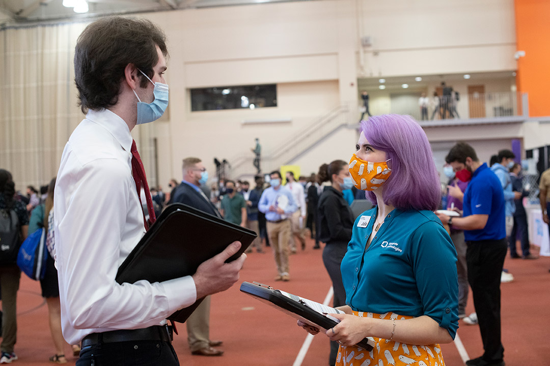 student and recruiter talking at a career fair.
