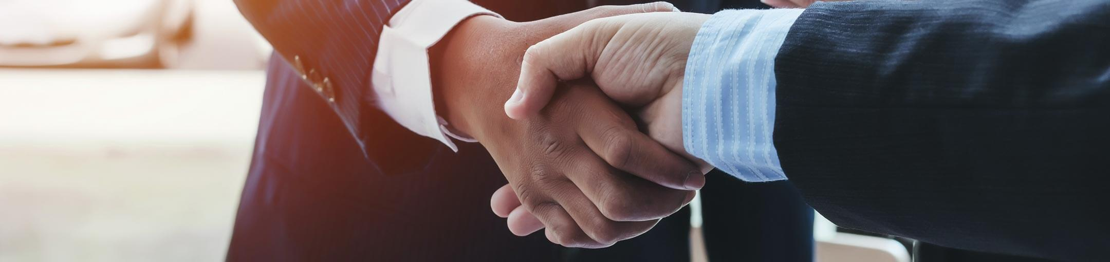 Two hands of people wearing suits shake hands.