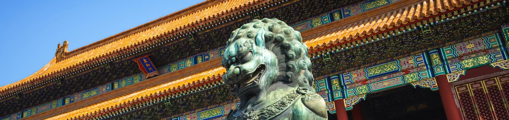 Ornamental Chinese building with lion statue in front of it.