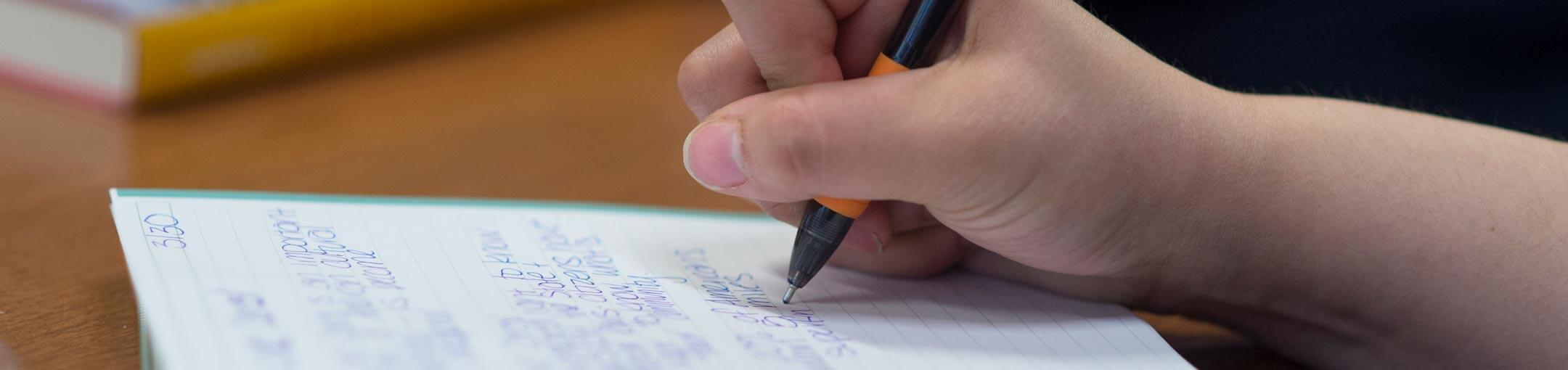 Hand holding pen writes on lined paper on desk.
