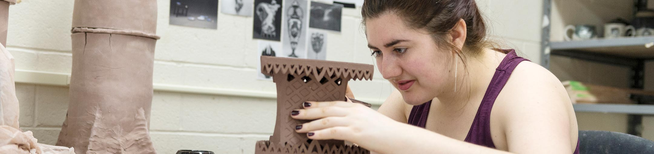 Student creating intricate lattice in ceramic sculpture.
