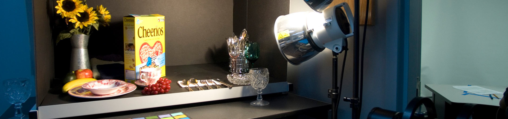 Desk with spotlight on plate, sunflowers in vase, utensils, glasses, and Cheerios cereal.