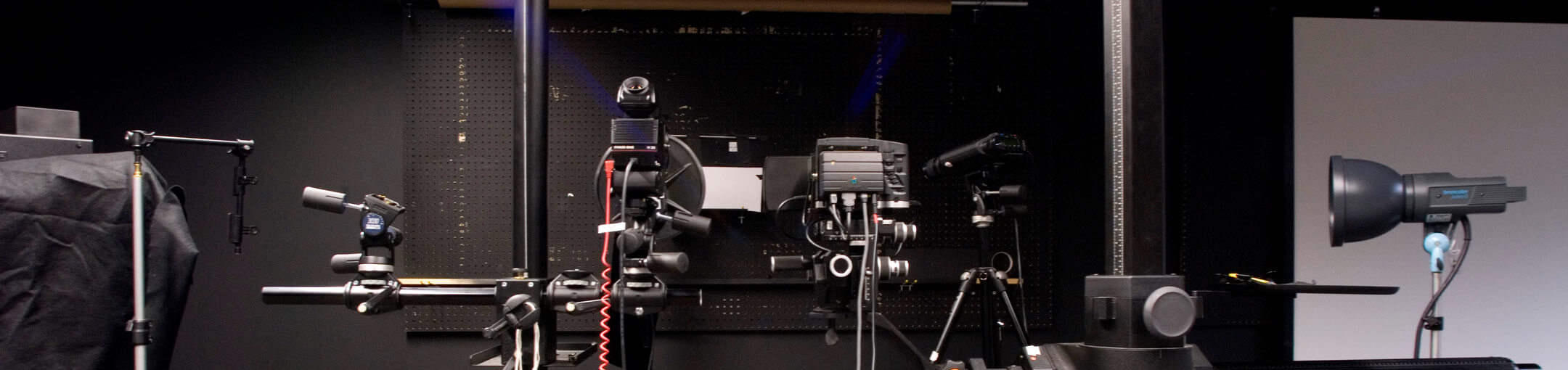 Several pieces of camera and lighting equipment on tripod stands.