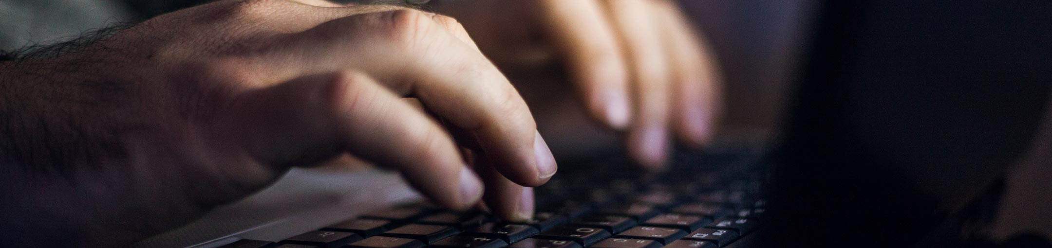 Close up of hands typing on laptop keyboard.