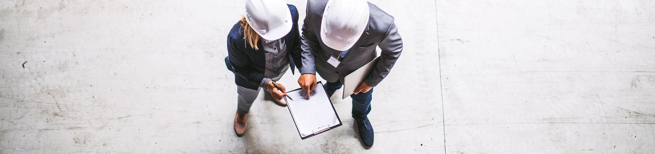 Top down view of two people wearing hard hats looking at a clipboard.