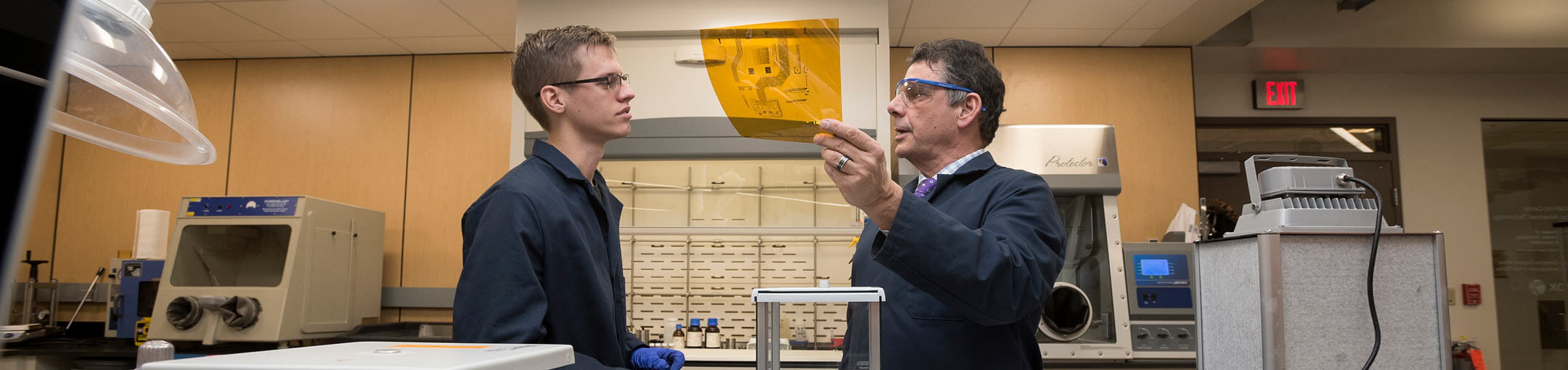 Student and professor talk over a schematic printed on amber-colored celophane.
