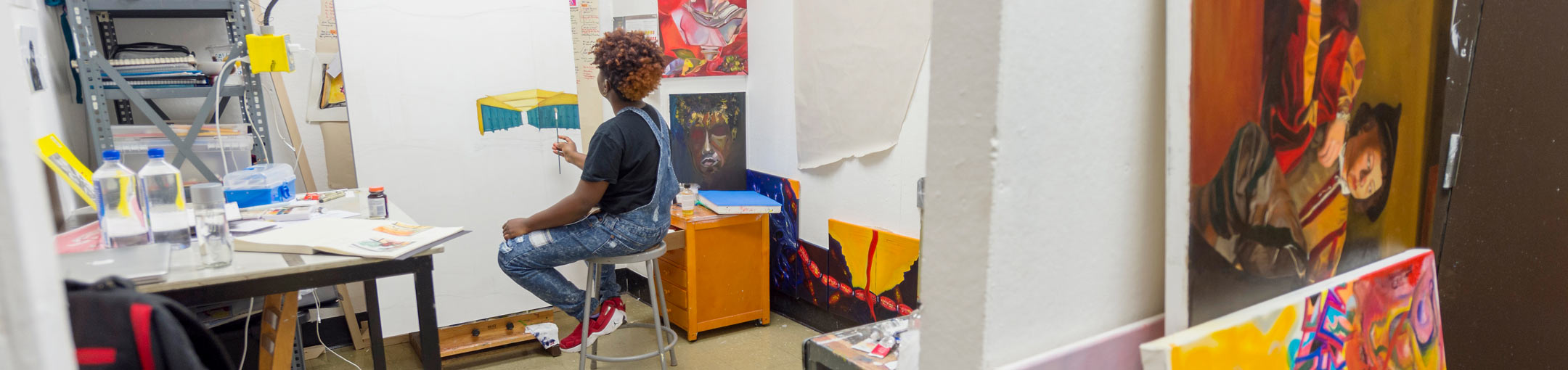 In a studio space, a student works on an architectural painting