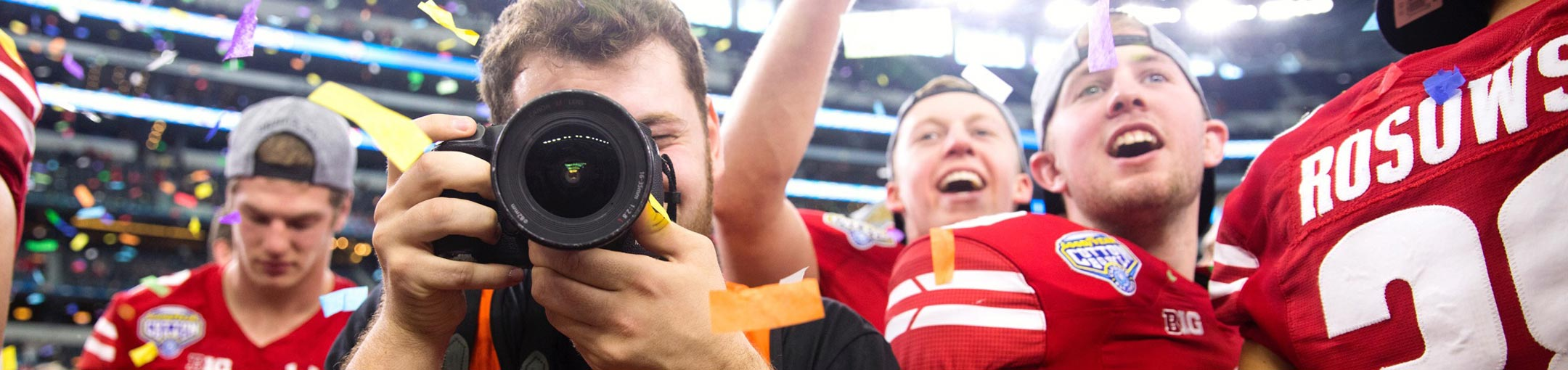 Football players in red stand behind a photographer who's camera is looking straight ahead at the viewer