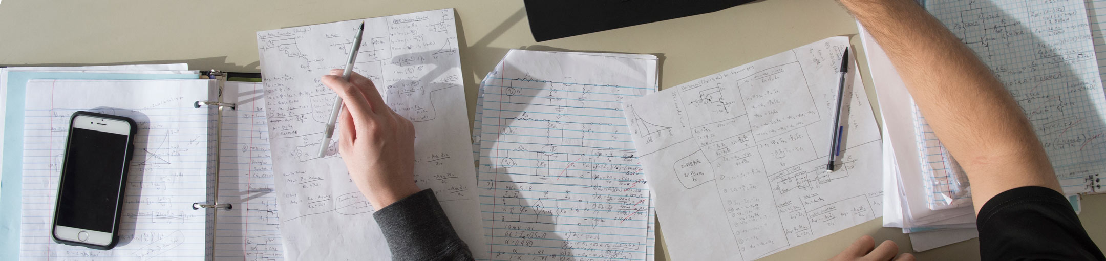 A closeup of two people working on solving math problems in their notebooks.