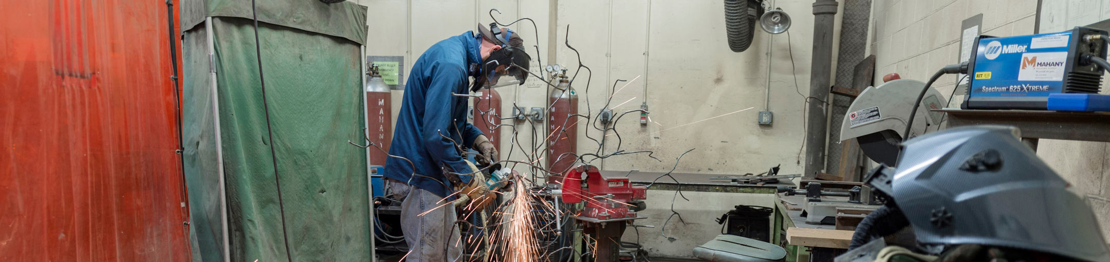 Student creates sparks from grinding a tree-like metal sculpture