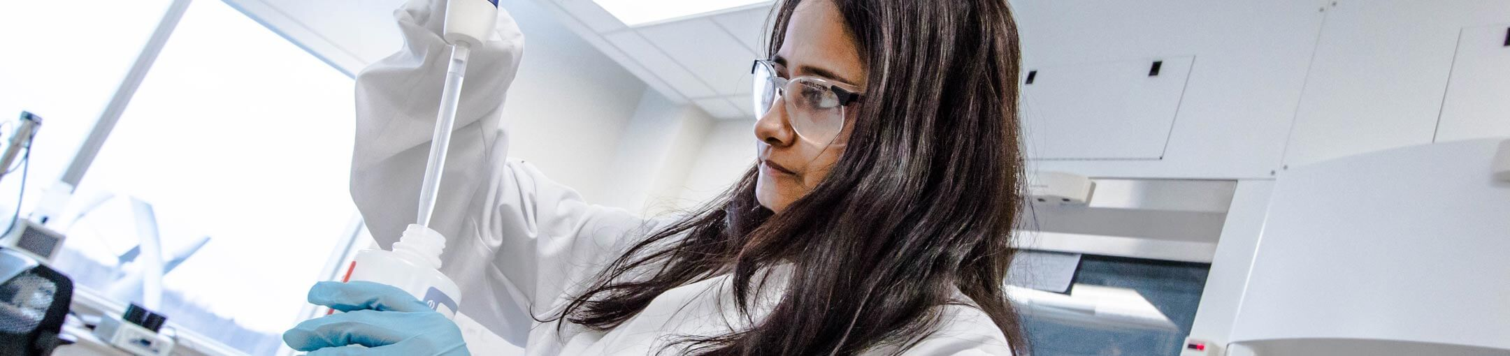 A student with long brown hair in a lab uses a pipette to put liquid into a bottle.