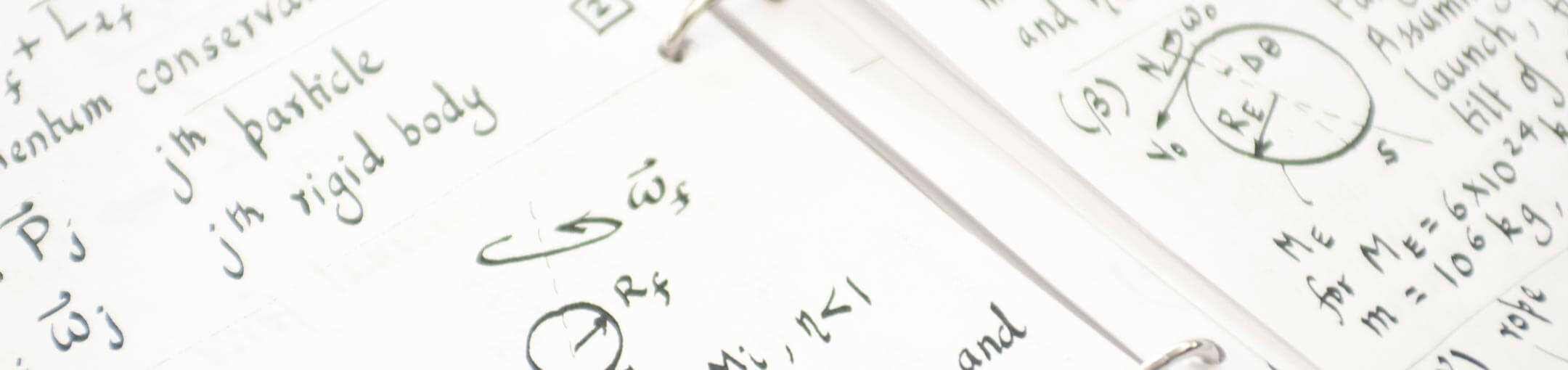 Close up of a 3-ring binder opened to written notes and formulas.