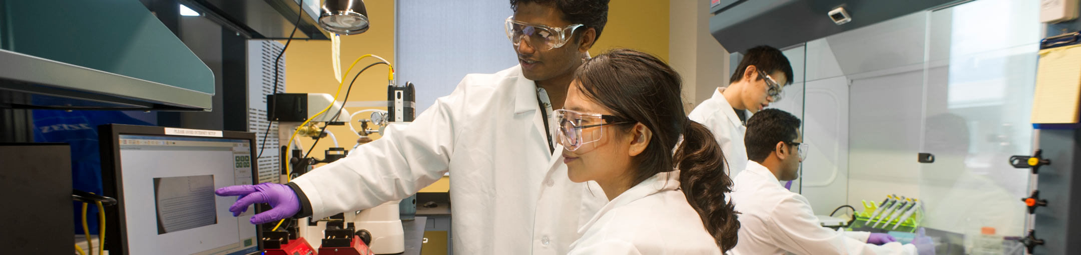 Students work in a lab. The two foreground students are looking at a computer monitor.
