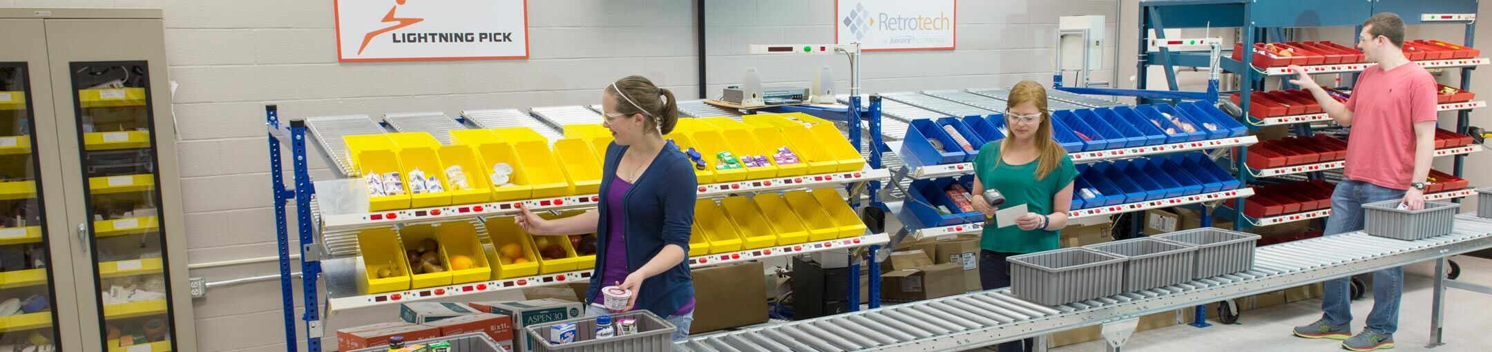 Students stand in front of three shelves of bins. The bins are yellow, blue, and red.