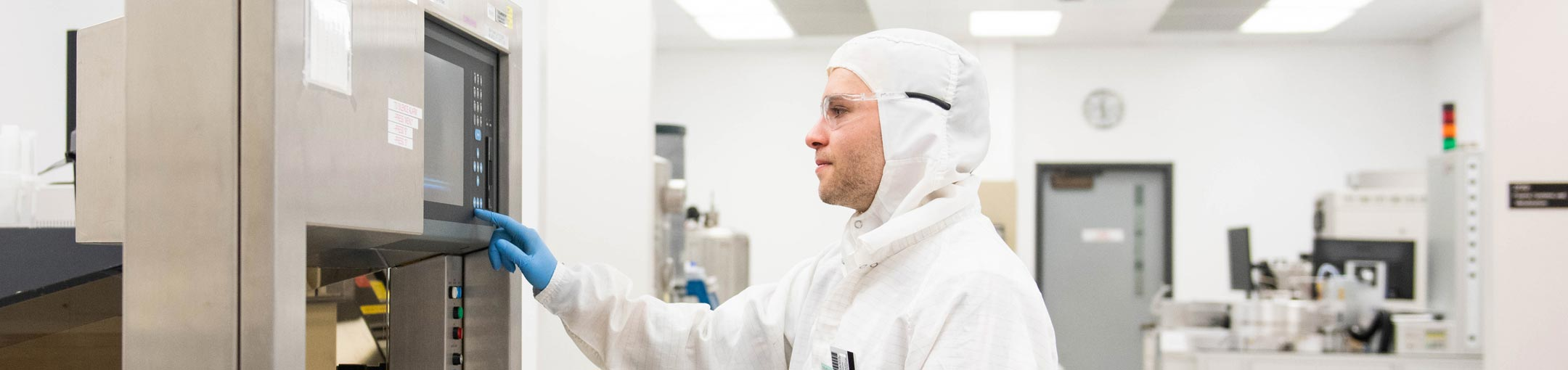 A student wearing a cleanroom suit presses a button on lab equipment