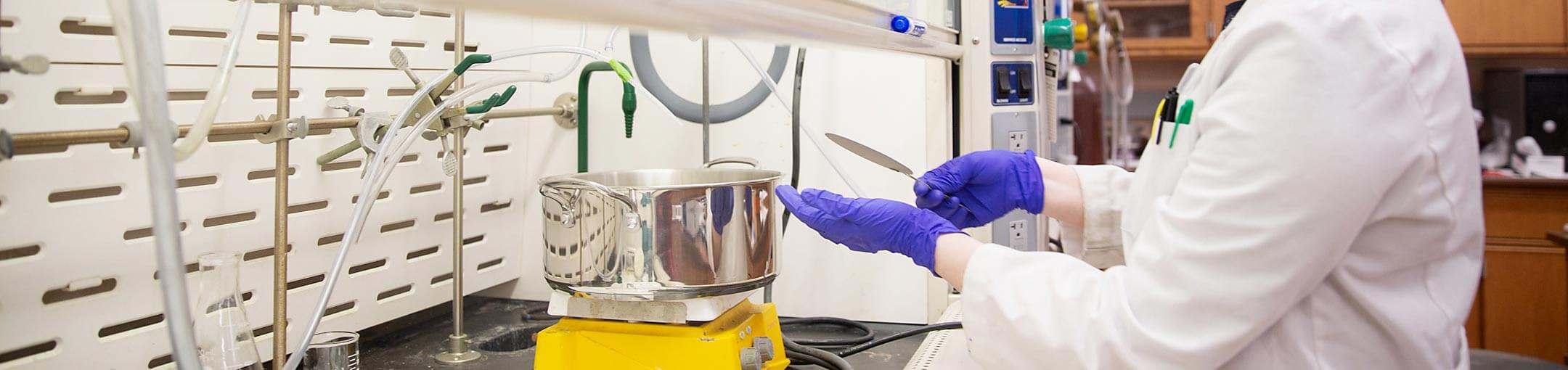 Student with purple gloves working in a lab.