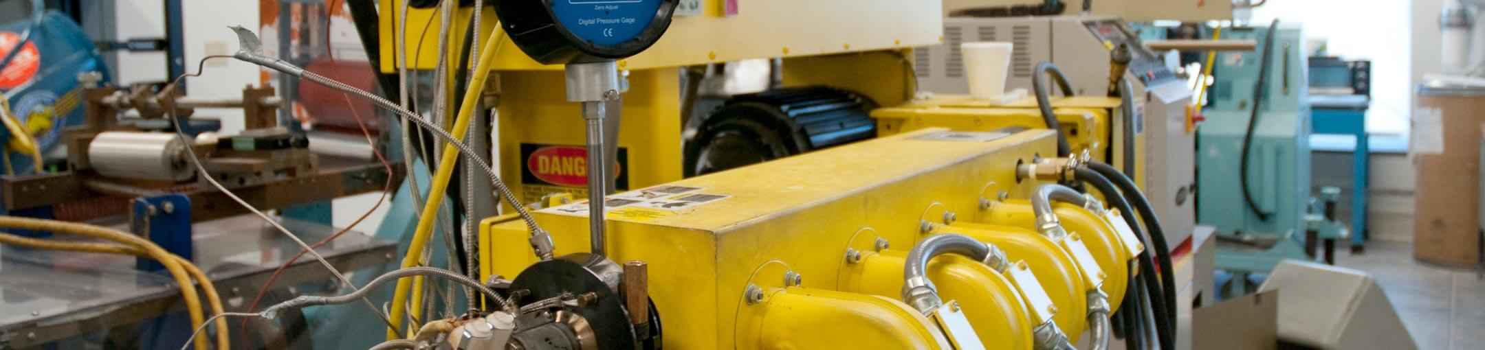 Close-up photo of yellow manufacturing equipment.