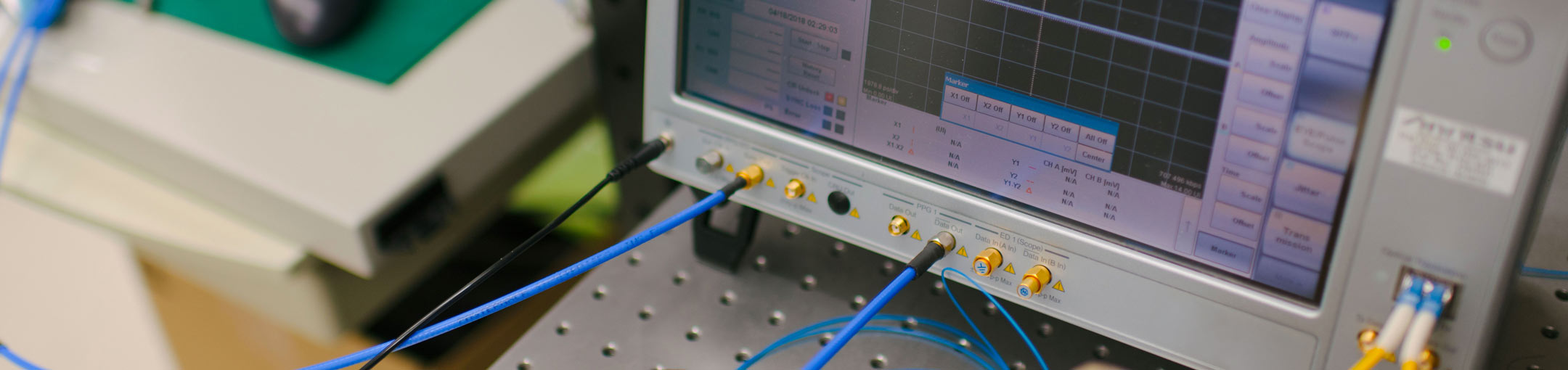 Close-up of wires going into a machine that appears to be some sort of voltage or audio monitor
