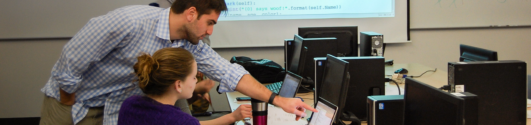 Professor helping a student at a computer in a lab.