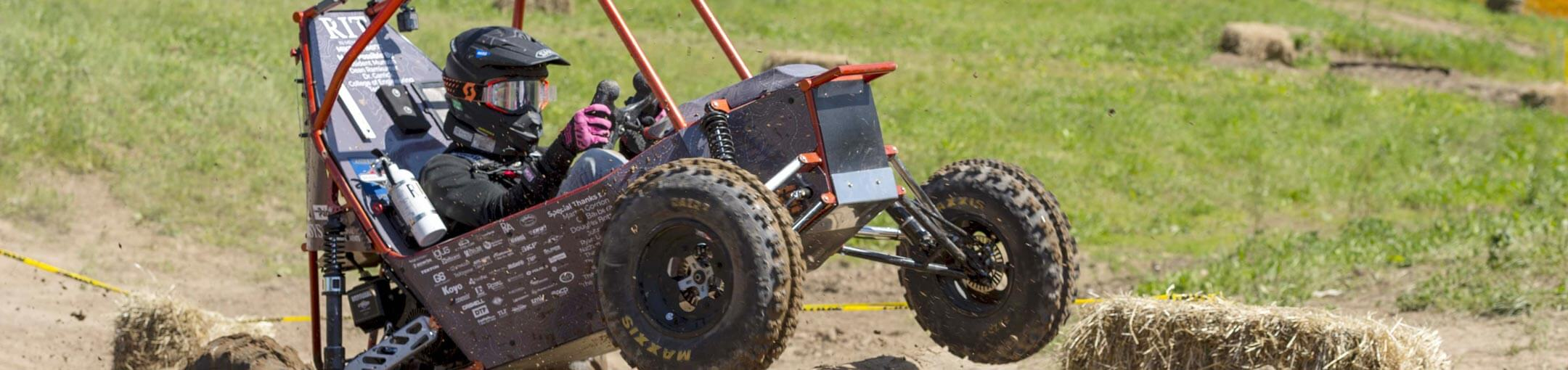 A helmeted student rides in the RIT Baja car.