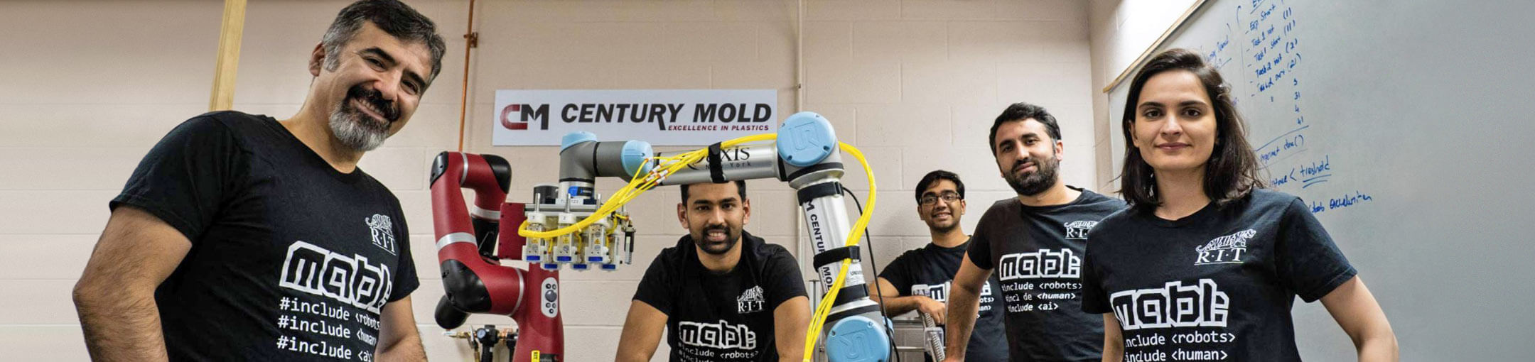 A group shot of people surrounding a robotic arm labeled Century Mold.