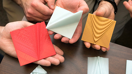 hands holding colorful 3D-printed squares