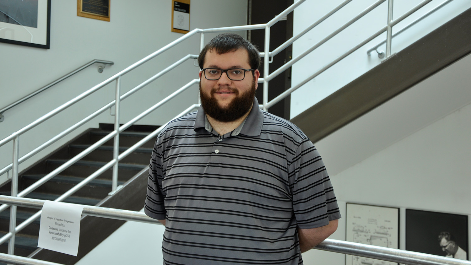 Student with beard and glasses wearing striped polo shirt stands near stairwell