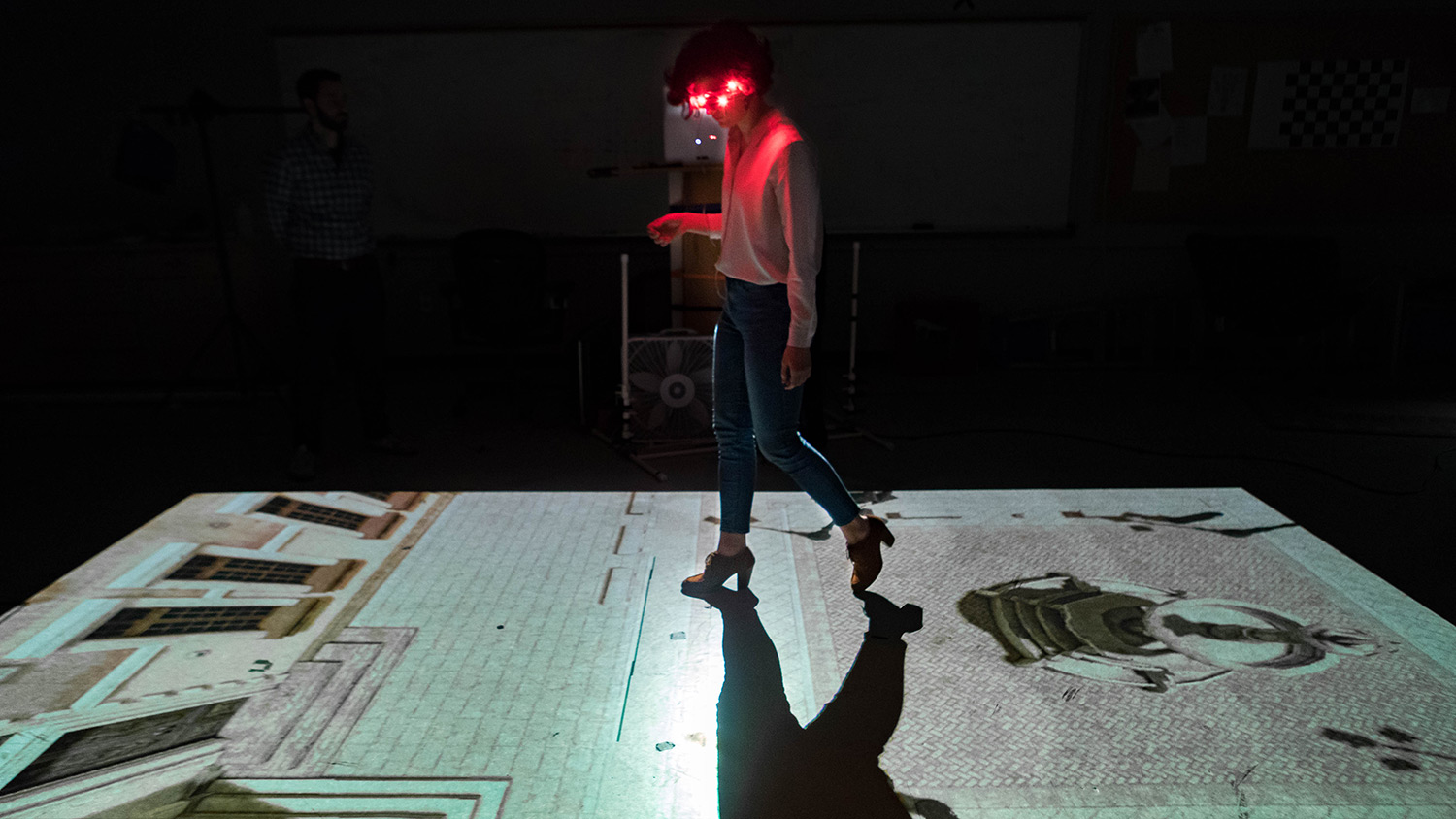 Student wearing lighted headset walks as an image of a brick walkway is projected on the floor