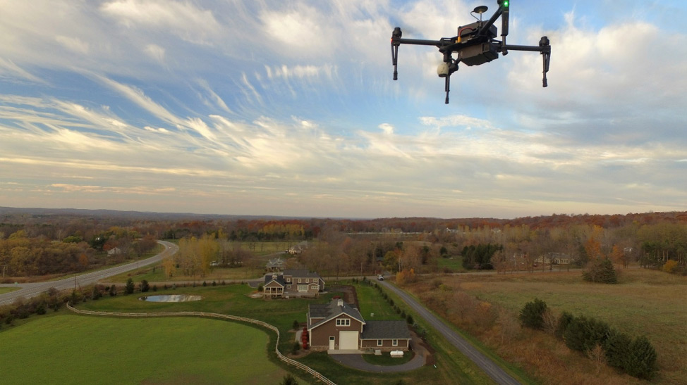 Drone flies over land with trees and two houses