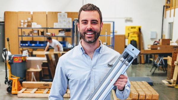 Man standing and holding a long, narrow light fixture