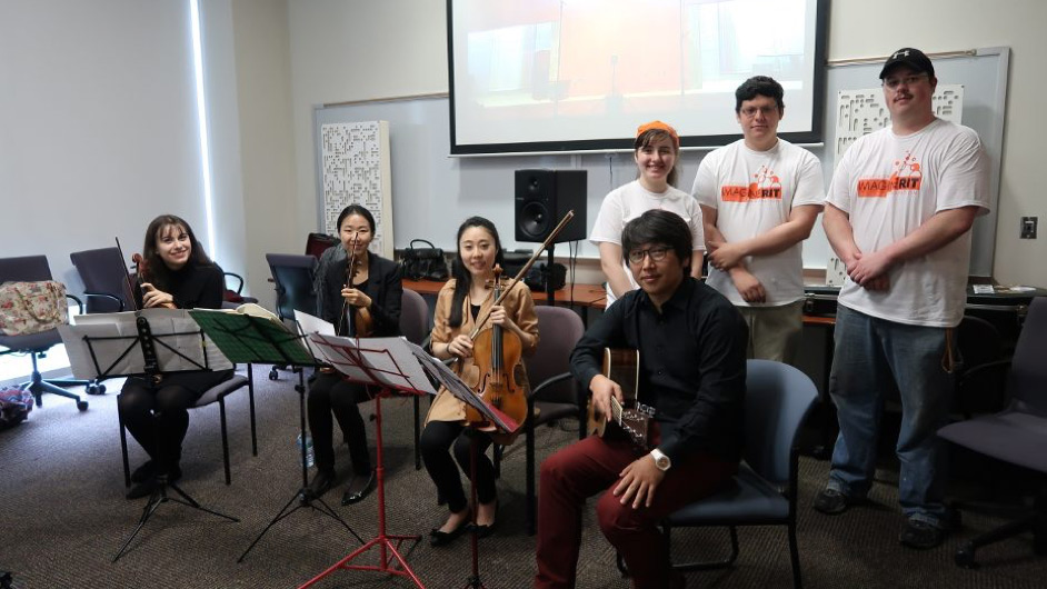 Group of people with four sitting in foreground holding musical instruments and three standing in background