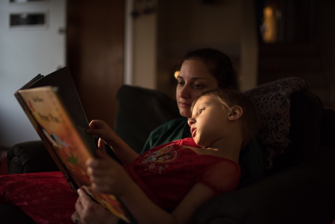 A photo of a young girl reading a book with her mother.