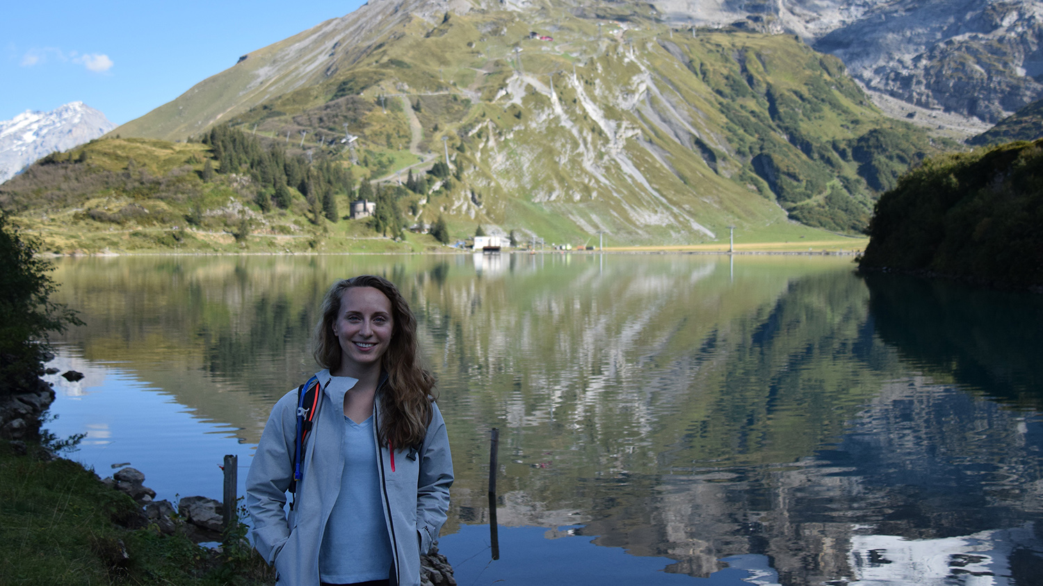 Alumna Victoria Scholl in front of a lake and mountain in Switzerland