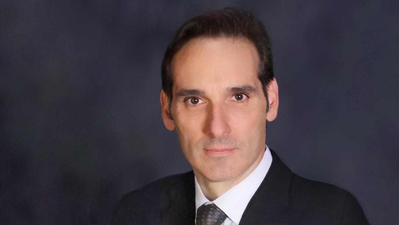 Portrait of James Tabbi on dark background