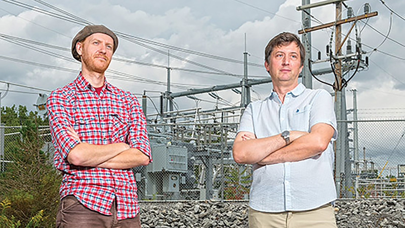 Researchers standing in front of an electrical grid