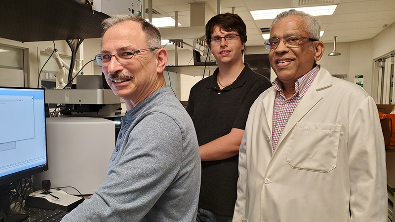 student standing with faculty and staff member in lab
