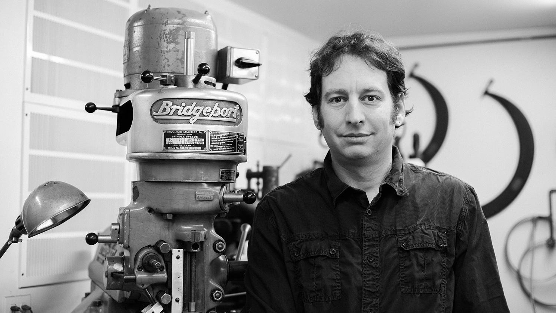 Peter Harrison stands next to a machine in his studio, where he creates unique furniture design.