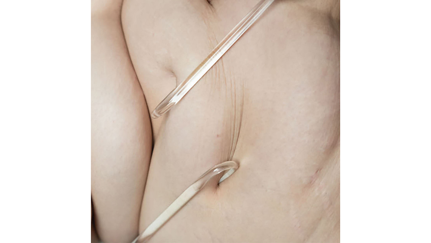 Glass hooks pull on flesh to demonstrate the material's fragility.