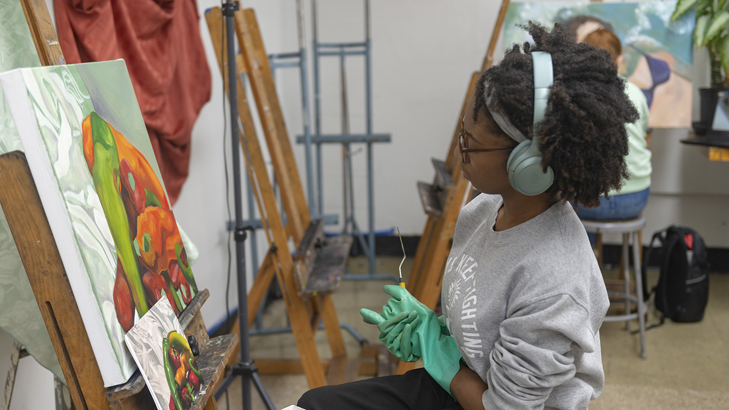 A student works on a painting in a studio.