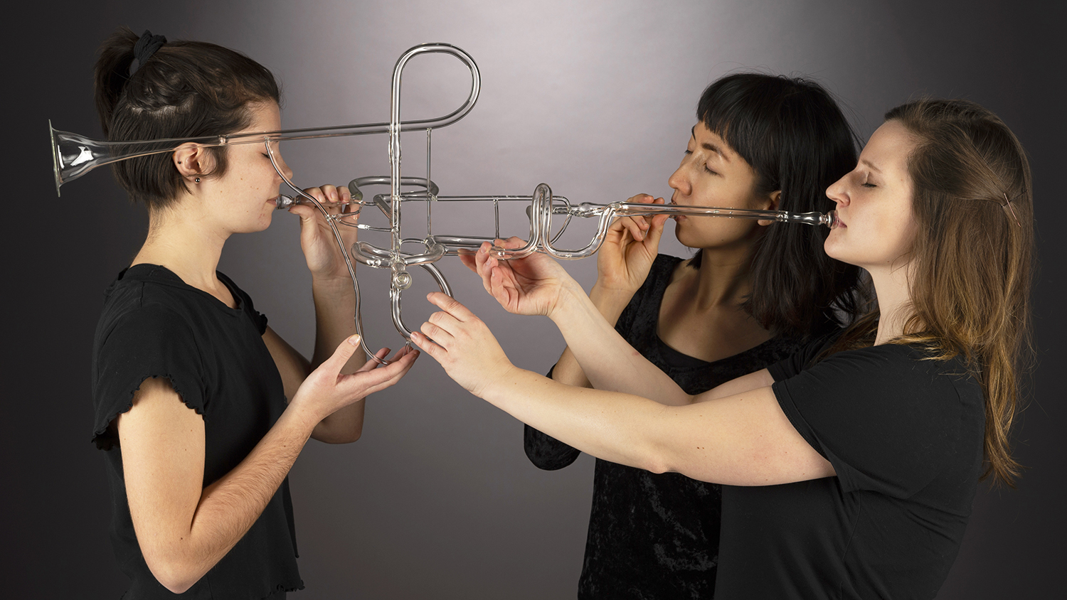 Three people play a glass trumpet that makes noise similar to a brass trumpet. The piece was designed to be an interactive art and music experience.