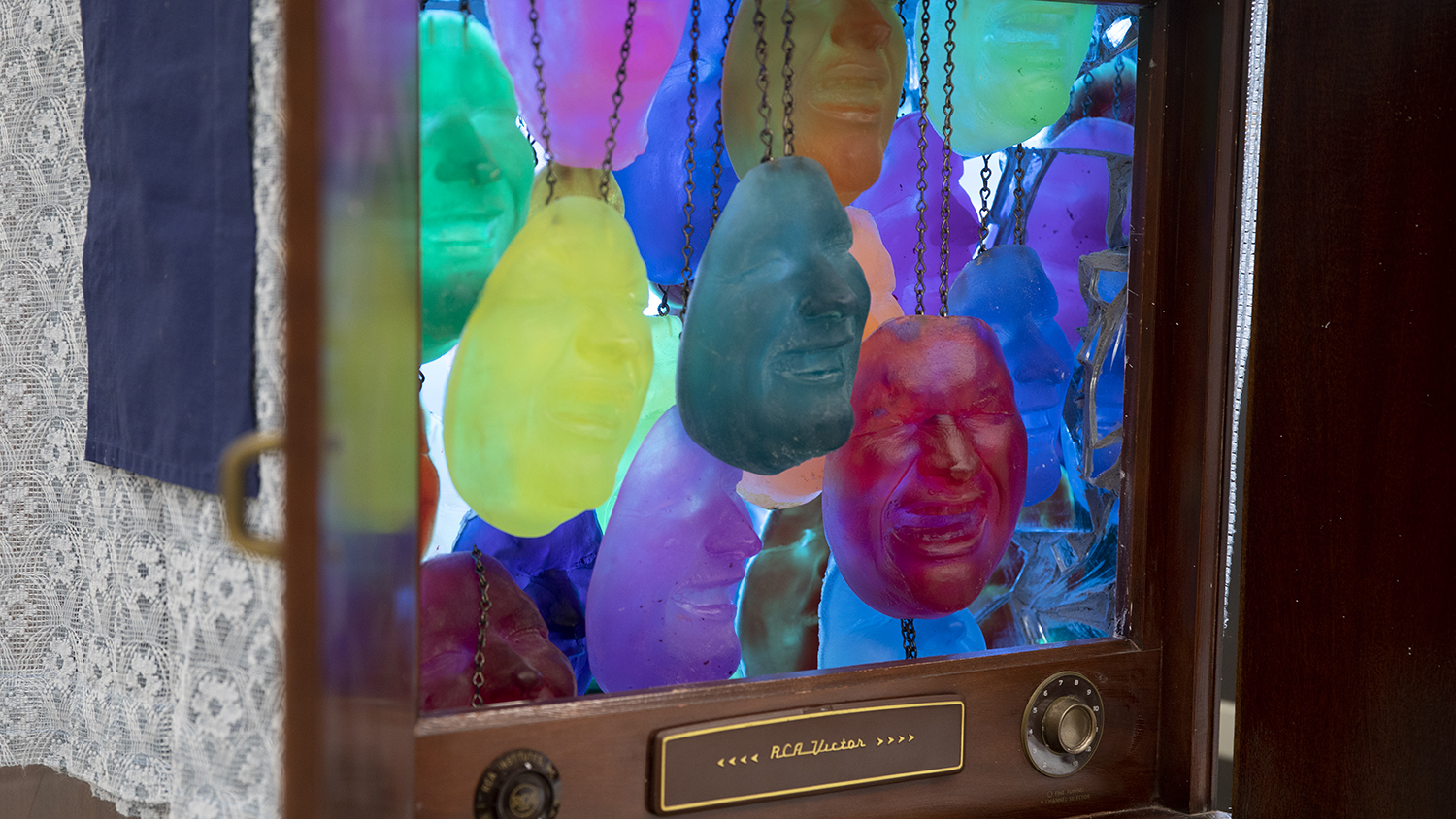 A grouping of colorful sculpted masks dangle from chains inside a retro television.