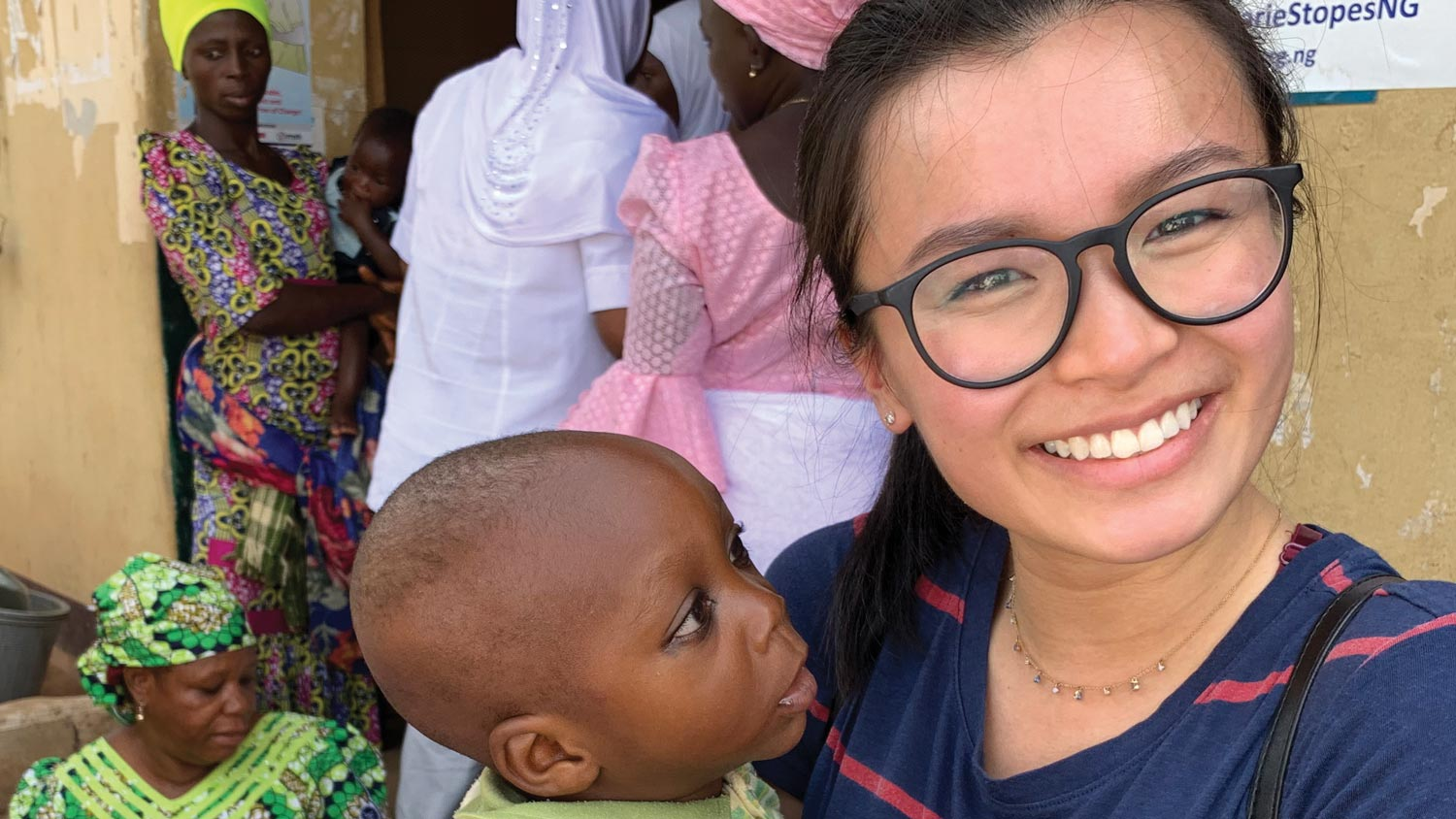 Janice Fung holds an infant outside of a health clinic in Nigeria.