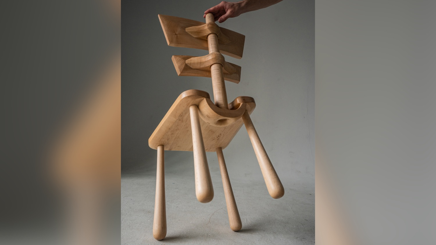 A finely crafted chair is held on two legs.