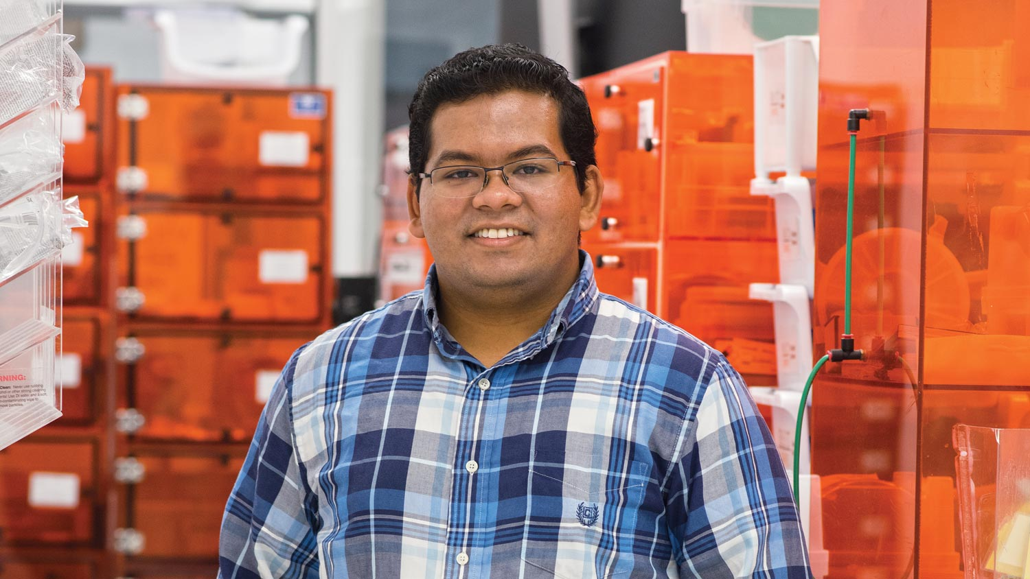 S M Huq, a microelectronic engineering major, stands in a lab with several transparent orange boxes.