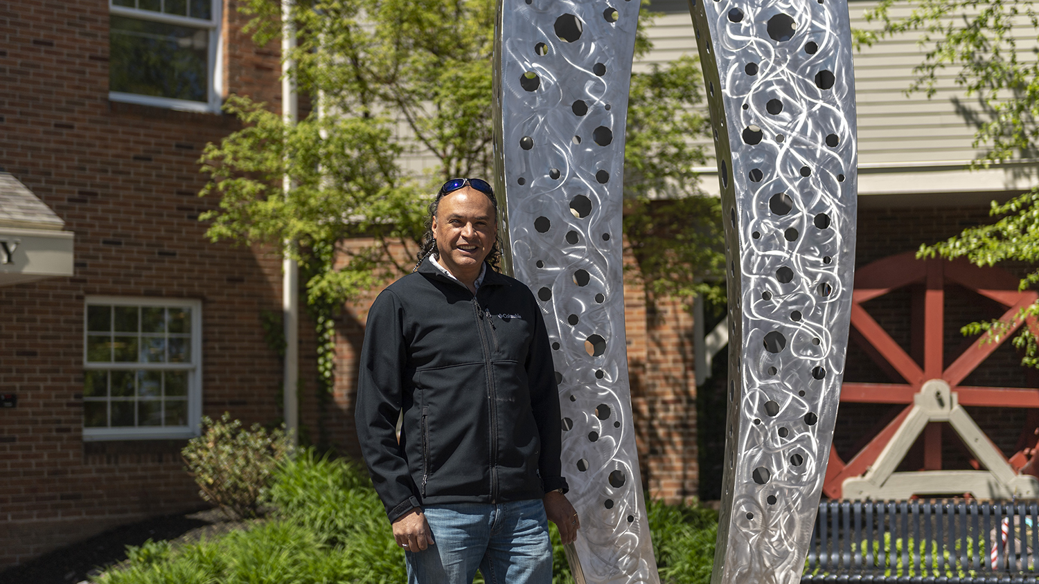 Carlos Caballero-Perez stands next to the public sculpture he created in Fairport.