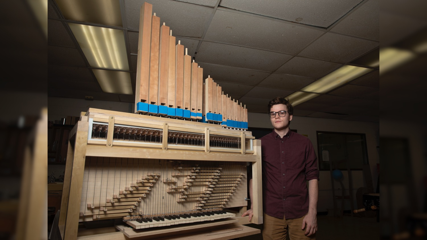 Student Kelly Cleveland poses next to his custom-built pipe organ.