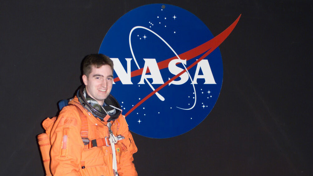 Paul Reichert stands in a space suit in front of a NASA wall decal.