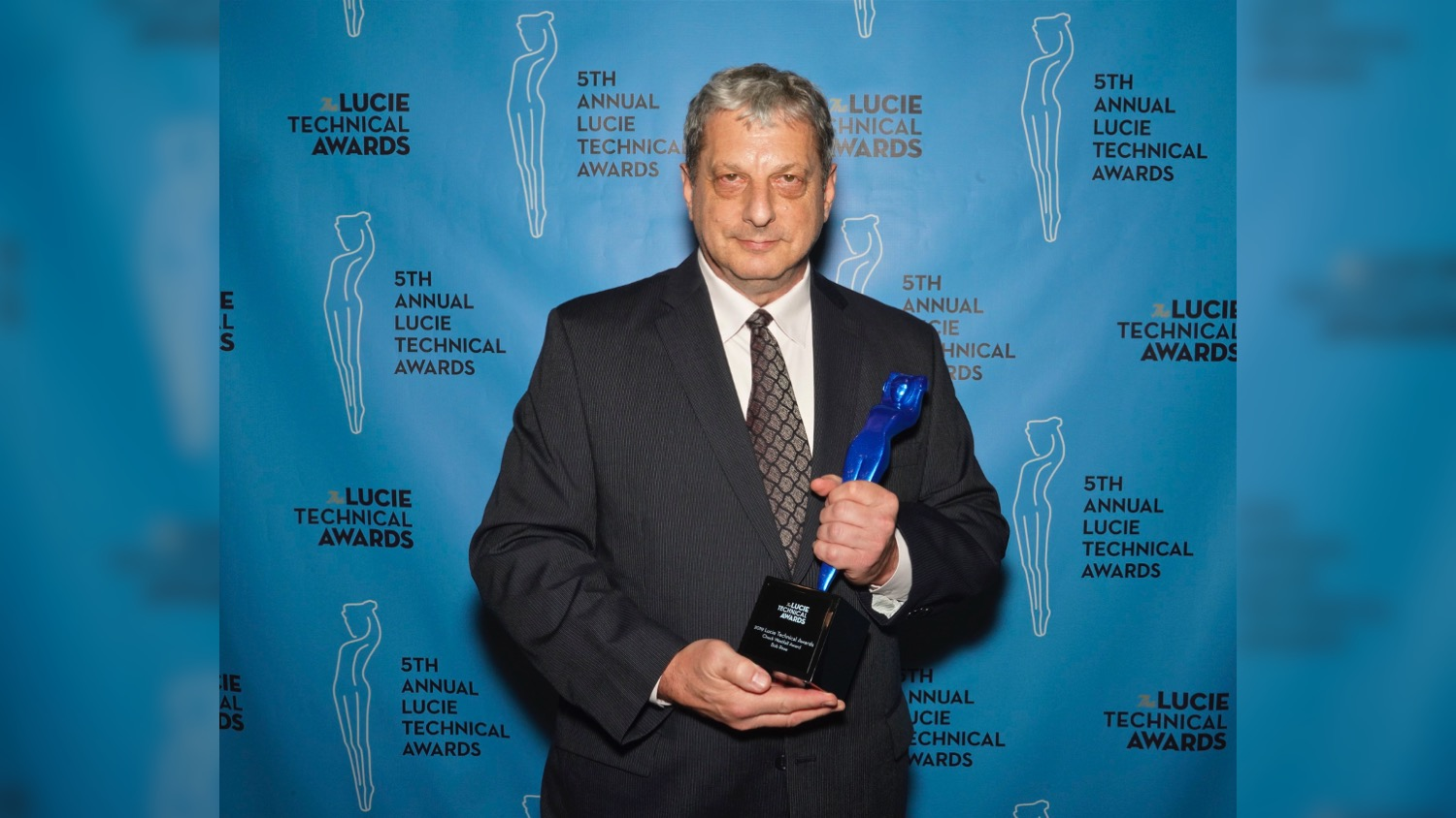 Faculty Bob Rose, dressed in a suit and tie, holds his Chuck Westfall Technical Education Award at the Lucie Awards. He won the award for advancing the photographic industry.
