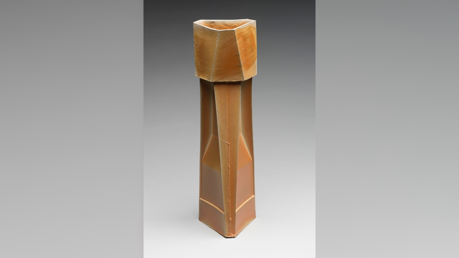 A tall wooden sculpture inspired by industrial architecture.